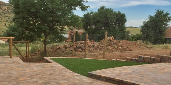 Backyard with artificial grass and a paver patio.