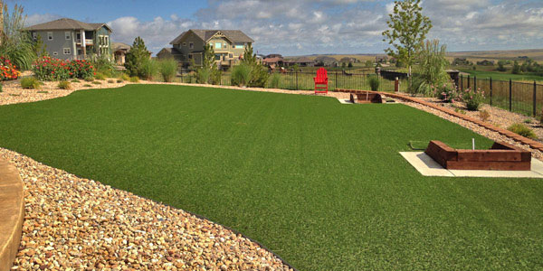 A horse shoe pit designed into a backyard with artificial turf.