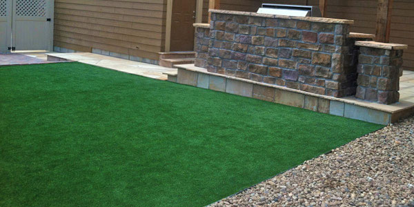 Colorado backyard with an outdoor kithchen and synthetic turf.