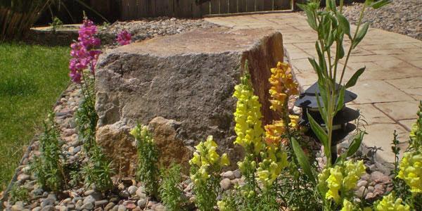 Flowers bordering decorative rock.