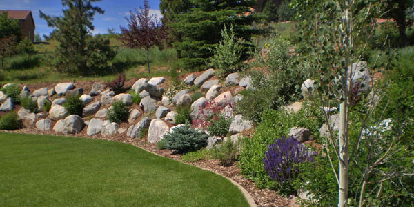 Curved rock garden by Backyards Plus.