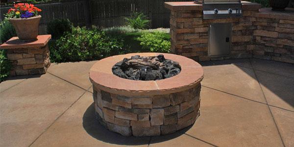 Natural gas fire pit on a decorative concrete patio.