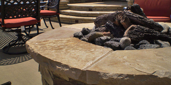 Natural gas fire pit with faux logs by Backyards Plus.