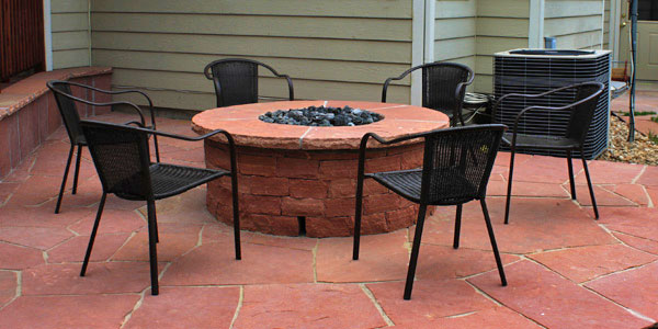 Flagstone patio and fire pit by Backyards Plus.
