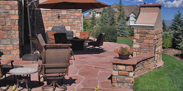 Outdoor living installation with an outdoor fireplace by Backyards Plus.