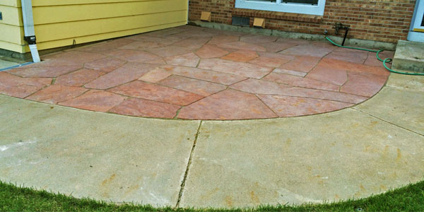 Pie shaped flagstone patio with concrete border by Backyards Plus.