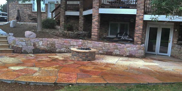 Flagstone patio, fire pit, and retaining walls by Backyards Plus.