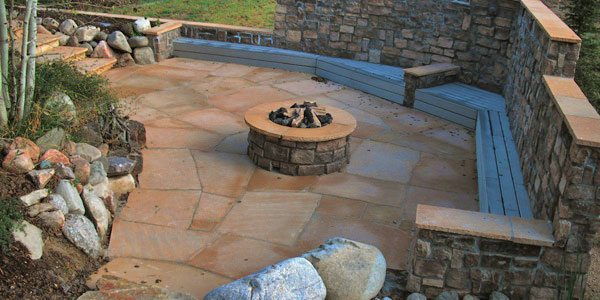 Flagstone patio with built in seating in Colorado by Backyards Plus.