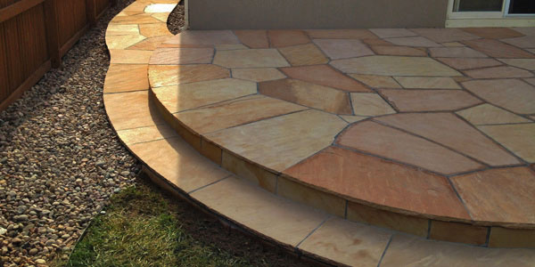 Detailed, round edged, flagstone patio by Backayrds Plus.