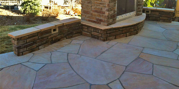 Outdoor fireplace on a flagstone patio installed in Denver by Backyards Plus.