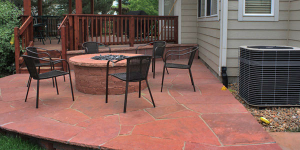 Flagstone patio with fire pit by Backyards Plus.
