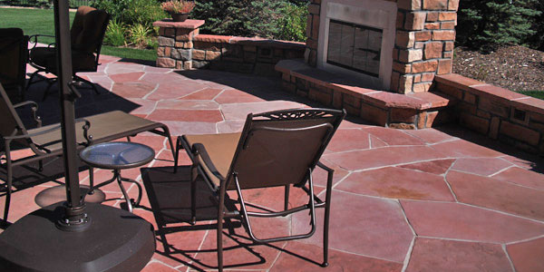 Flagstone patio and outdoor fireplace by Backyards Plus.