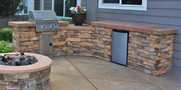 Outdoor kitchen with natural gas grill and outdoor refrigerator by Backyards Plus.