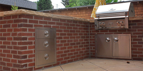 Outdoor kitchen with built in drawers by Backyards Plus.