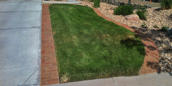 Decorative hardscape borders can spruce up a regular concrete driveway.
