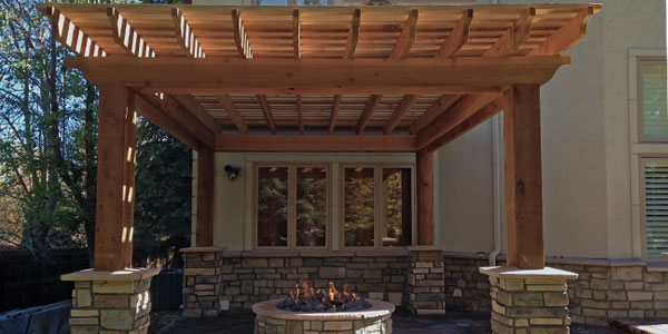 Shade structure for patio area with decorative stone half pillars.
