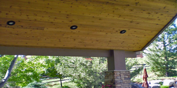Shade structure roof with lighting for an outdoor living area by Backyards Plus.