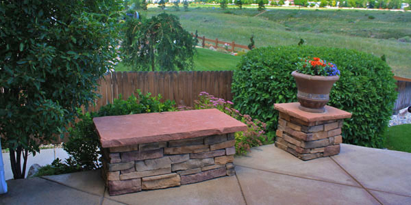 Short stone pillars for decoration paired with a stone seating bench