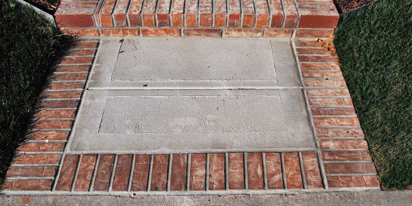 Cement steps with a brick border by Backyards Plus.