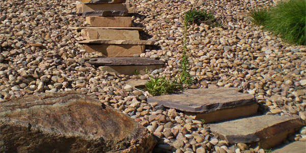 Stone stairs in river rock by Backyards Plus.