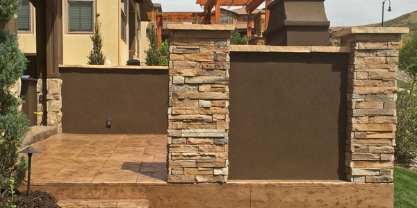 Stamped concrete patio in Highlands Ranch with an outdoor fireplace.