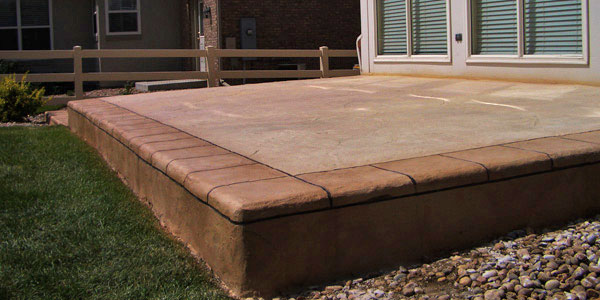 Cement patio with a stamped concrete border by Backyards Plus.