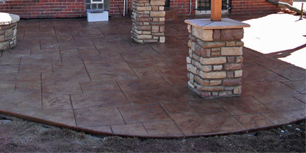 Stamped concrete under a shade structure with stone pillars.