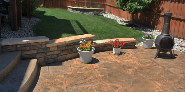 Denver backyard with half grass and half stamped concrete.