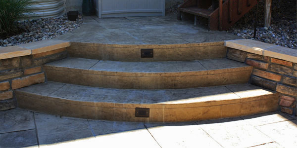 Pie shaped stamped concrete steps with built in lighting.