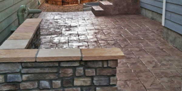 Stamped concrete with a seating wall in a Denver backyard.
